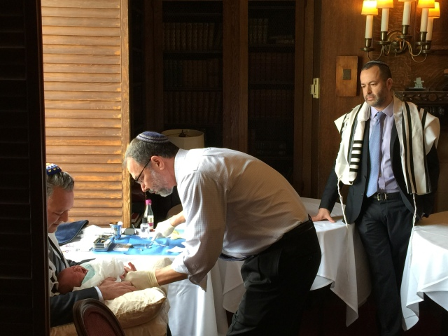 Father Nathan looks on as Rabbi Trager circumsizes his son who was held by his brother Mark.